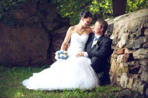 Svatební fotografie ženicha a nevěsty u staré zdi